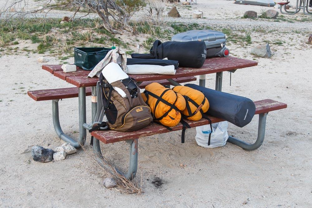 Roadtrip mit Zelt und Campingutensilien auf einem Tisch aufgereiht.
