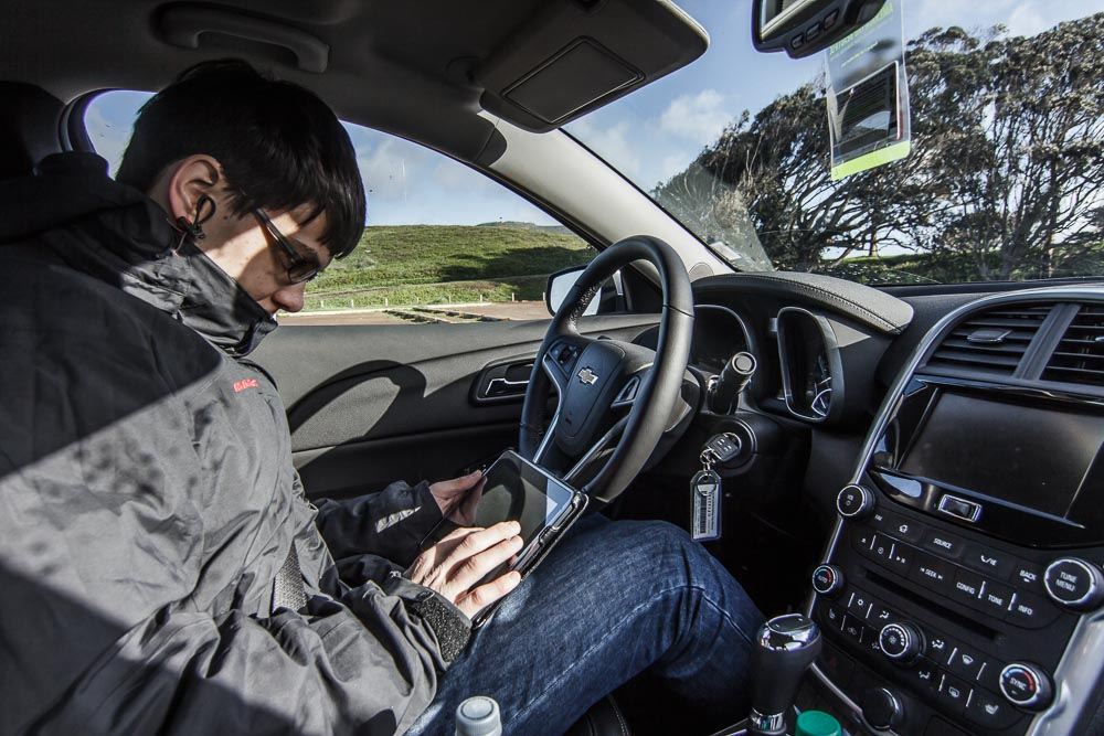 Christian auf dem Fahrersitz des Chevrolet Malibus beim Planen der Route.