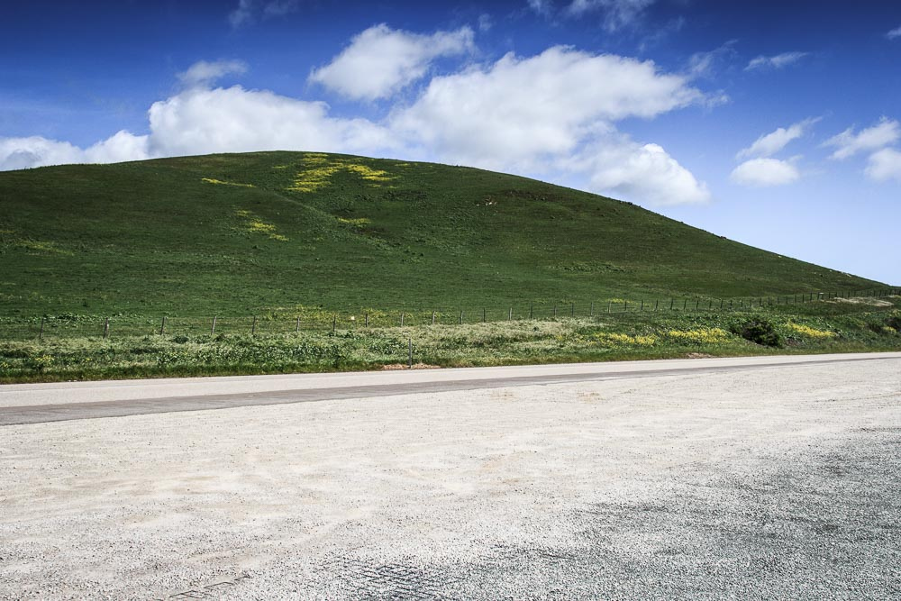 Grüner Hügel unter blauem Himmel am Highway One in Kalifornien