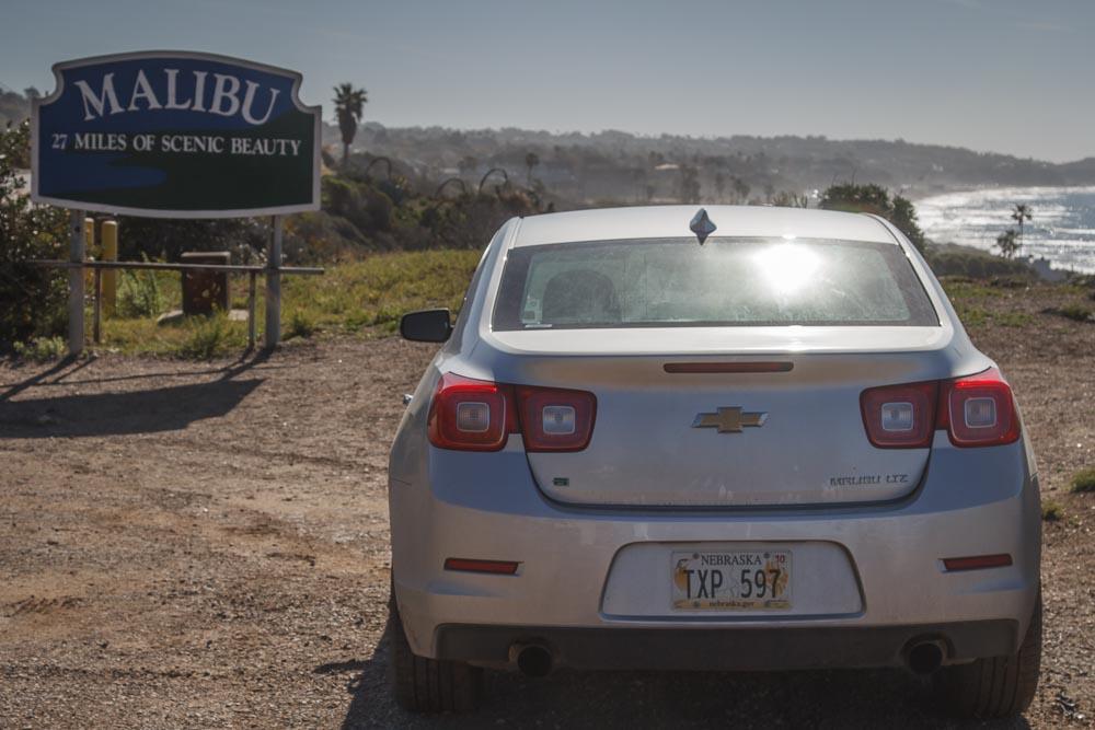 Silberner Chevrolet Malibu vor dem Stadtschild Malibus
