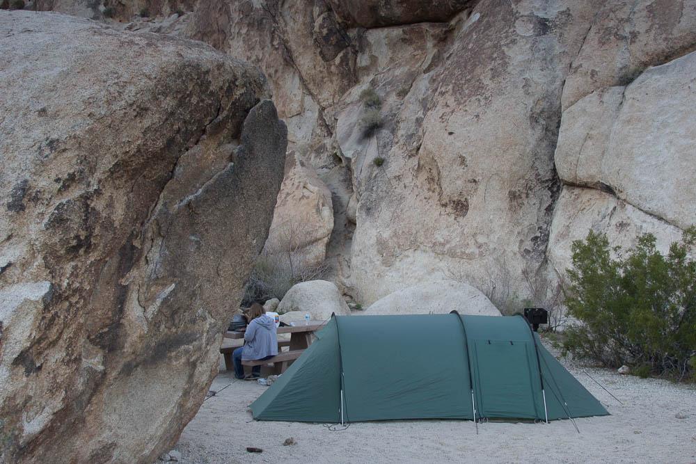 Tentsite mit grünem Tunnelzelt zwischen Felsen im Joshua Tree National Park