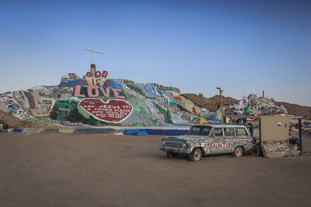 Salvation Mountain in Kalifornien nahe dem Salton Sea mit altem Auto im Vordergrund