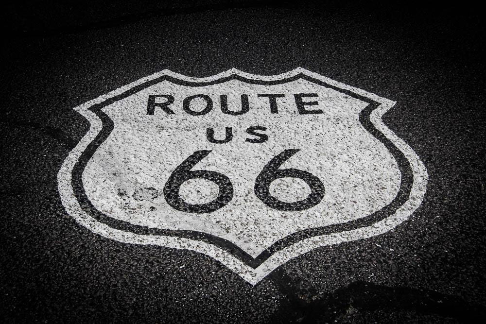 Weißes Route 66 Emblem auf schwarzem Asphalt. Einer unserer Top 10 der Sehenswürdigkeiten in Arizona.