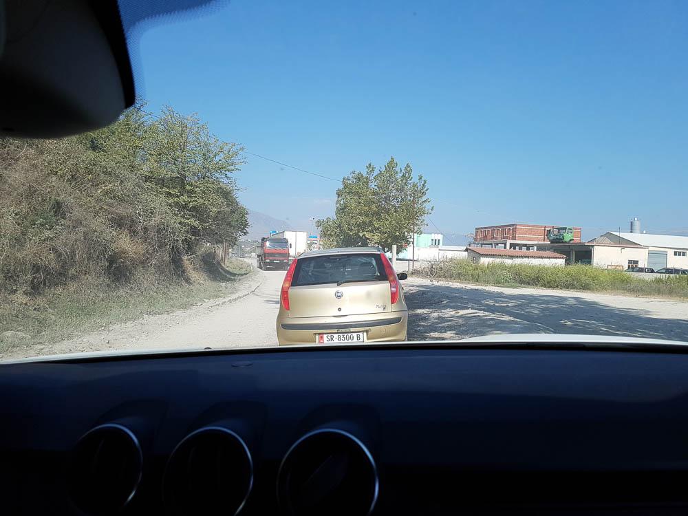Fotografiert aus dem Dacia Duster heraus ist die Schotterpiste zu sehen, welche als Umfahrung der Baustelle bei Gjirokastra dient. Vor uns ein Fiat Kleinwagen und ein LKW, welcher uns entgegenkommt.
