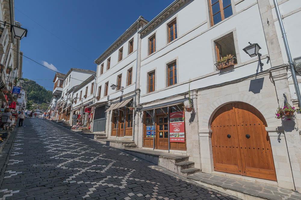 Gepflasterte Straße in Berats Altstadt im Herzen Albaniens. Die weißen Häuser sind zum größten Teil bereits saniert und die aufgrund der steilen Straßen und Gassen, haben die Fußgängerwege Treppen.