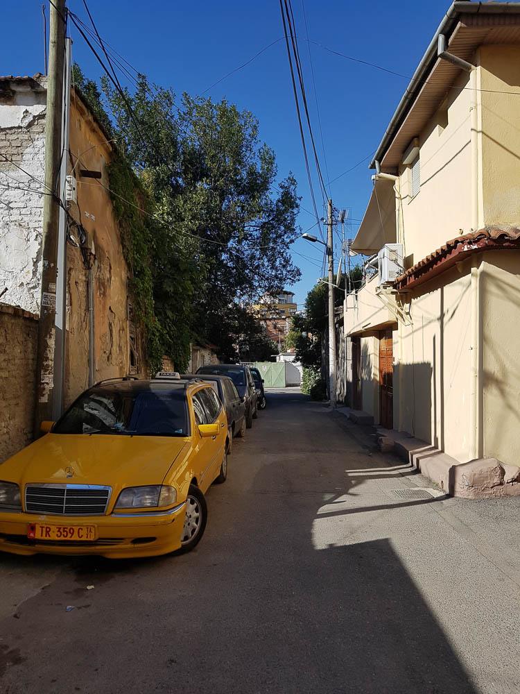 Nebengasse in Albaniens Hauptstadt Tirana mit einem der gelben Taxis im Vordergrund.