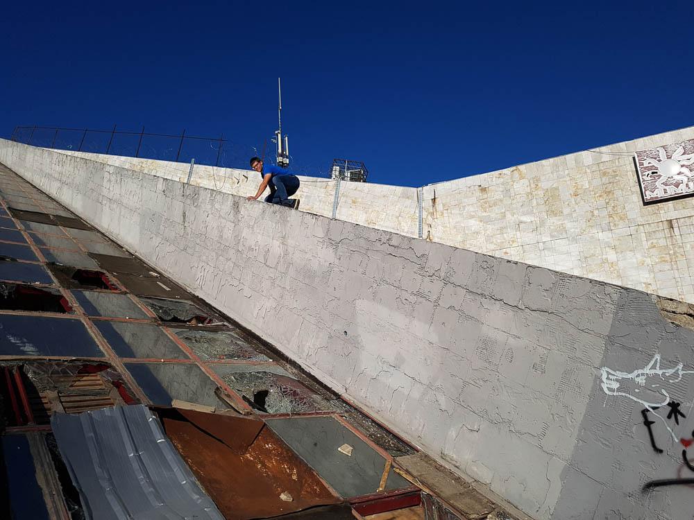 Mann klettert auf das Dach der Pyramide in Tirana.