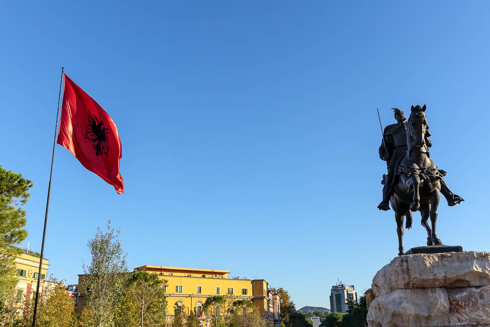 Die Flagge Albaniens neben der Statue Skanderbegs am Skanderbegplatz in Tirana.
