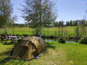 Zelt an kleinem Bach auf grüner Wiese in der Natur