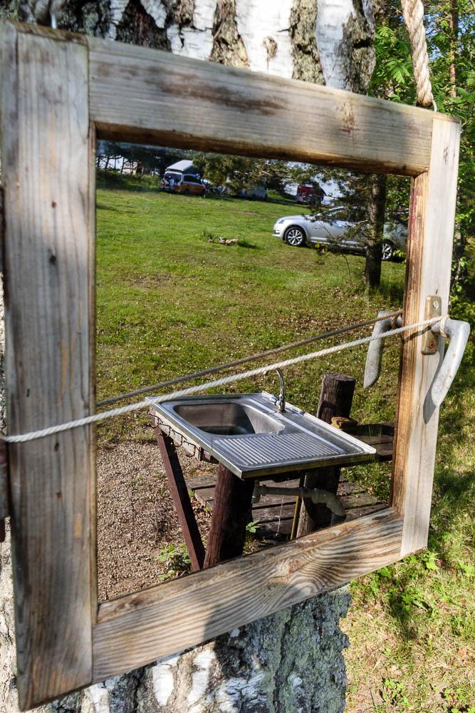 Outdoorbad  mit Spiegel und Blick auf einen der Waschplätze am Kempings Melnsils
