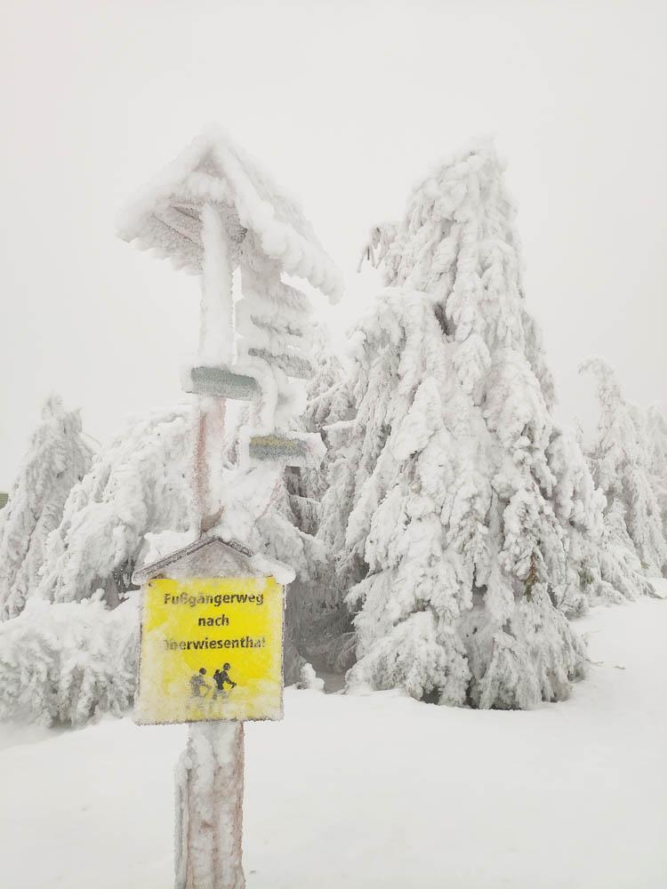 Verschneiter Wegweiser nach Oberwiesenthal auf dem Gipfel des Fichtelbergs in Sachsen