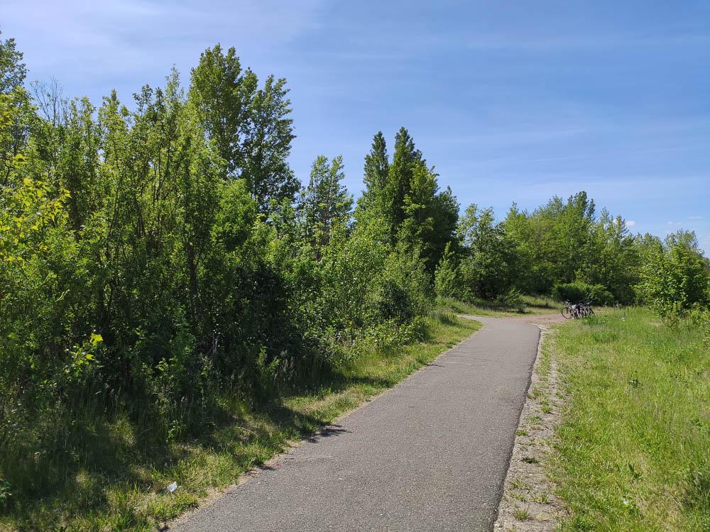 Fahrrad- und Wanderweg für Wandern in Sachsen-Anhalt rund um den Grokaynaer See bei blauem Himmel und mit zwei Fahrrädern im Hintergrund.
