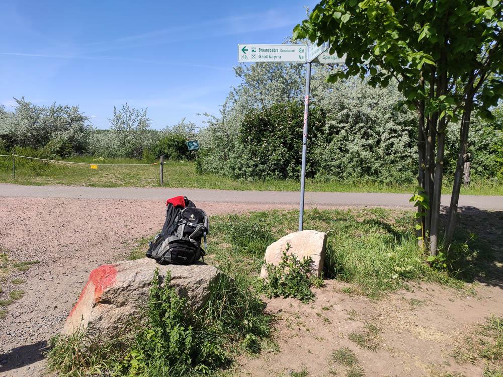 Wegweiser am Großkaynaer See mit Rucksack auf einem Stein im Vordergrund.