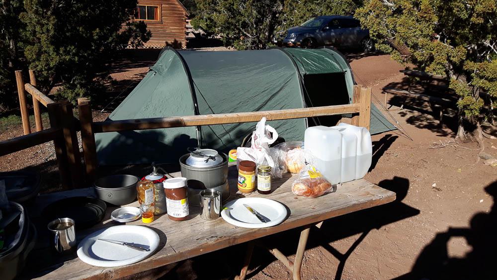 Frühstückstisch beim Roadtrip mit Zelt auf einem hölzernen Tisch