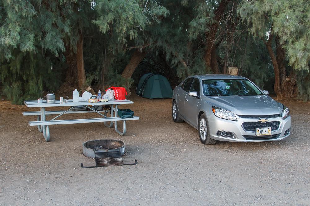 Tentsite am Furnace Creek Campground. Zelt steht im Schatten der Bäume. Es gibt einen Alutisch und eine Feuerstelle. Das Auto parkt am Platz.