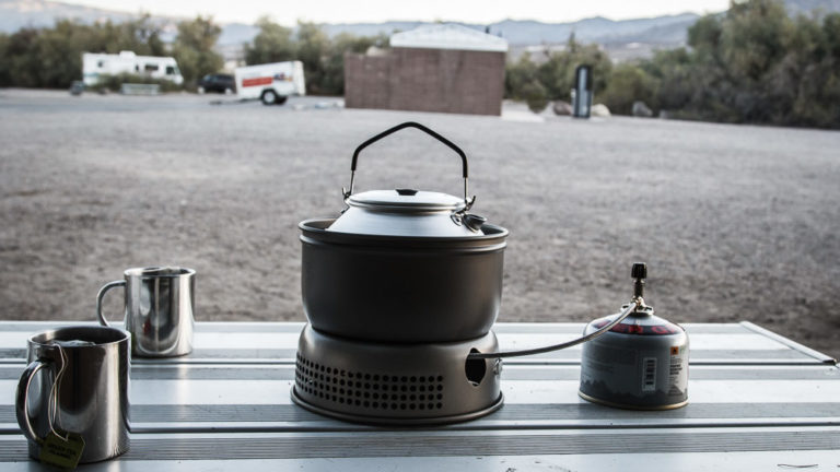 Zwei Tassen und Trangia-Sturmkocher mit Gasaufsatz auf einem Campingtisch des Furnace Creek Campground im Death Valley National Park.