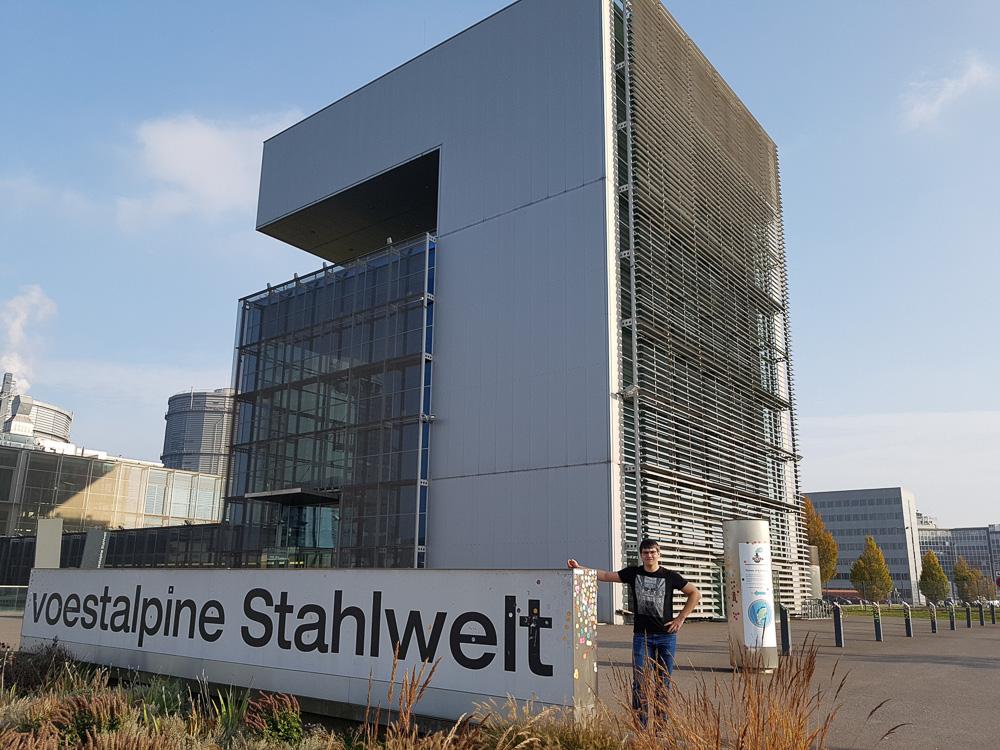 Christian vor dem Schild der Voestalpine Stahlwelten in Linz