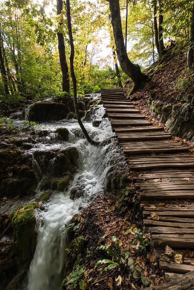 Bohlenweg entlang eines Wasserfalls beim Wandern bei den Plitvicer Seen