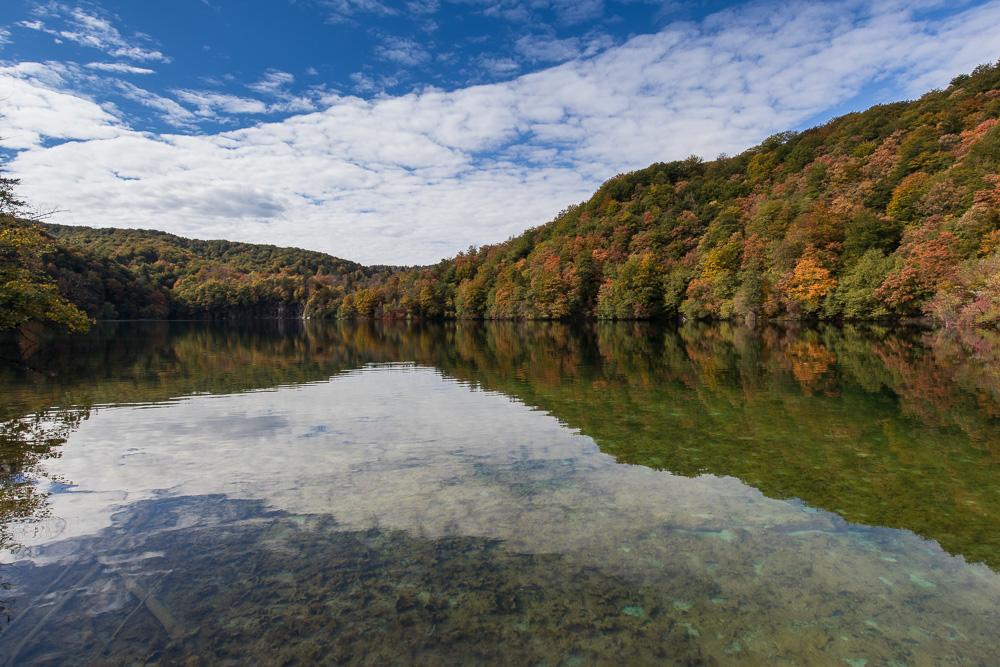 Die herbstlichen Bäume spiegeln sich im Wasser im Nationalpark Plitvicer Seen