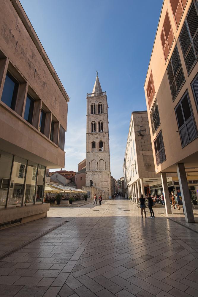 Der hohe Turm der Kathedrale Zadars von einer der schattigen Gassen aus gesehen