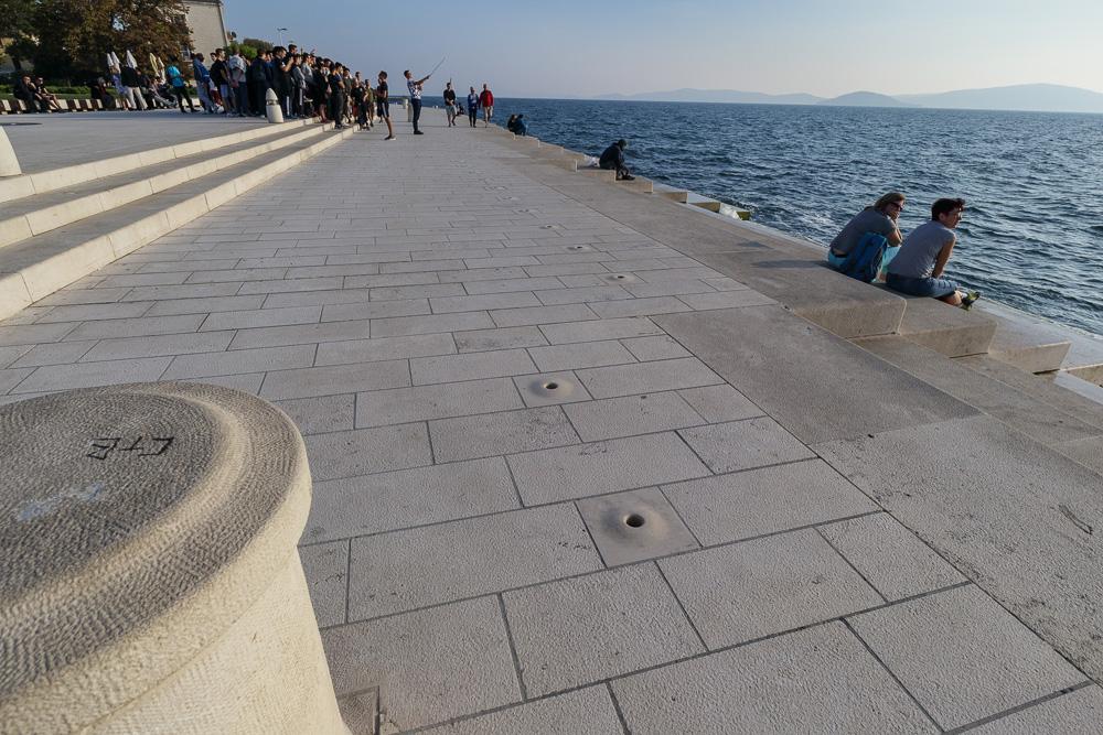 """Viele Touristen an der Meeresorgel. """"Hier sind die Orgelpfeifen gut zu sehen""""."""