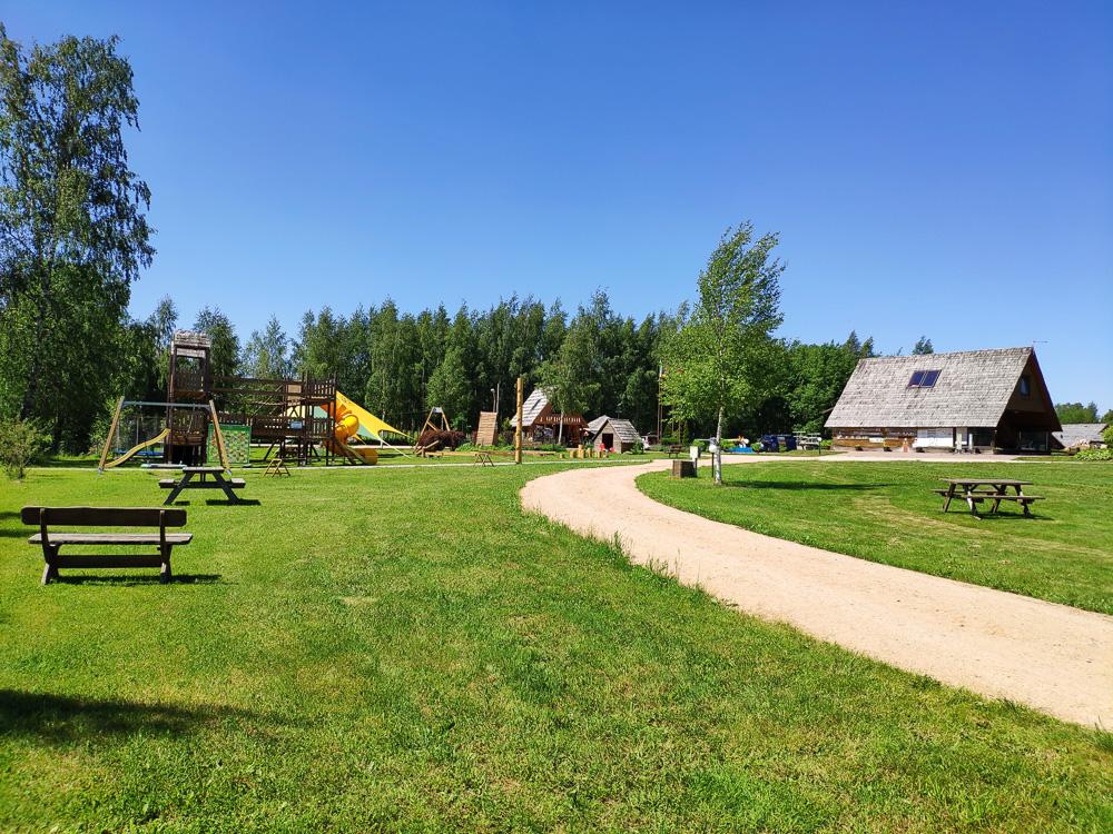 Die Zufahrt zu den großen Wiese mit Kinderspielplatz sowie die Rezeption und Sanitäranlagen im Hintergrund bei Camping Apalkalns