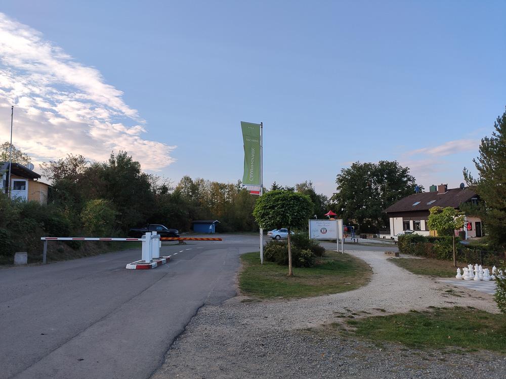 Zufahrt zum Campingplatz von innen aus gesehen. Im Hintergrund rechts das Restaurant mit der Rezeption