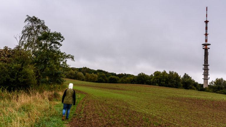 Pauline auf dem Wanderweg zum Helpter Berg mit dem Sendeturm im Hintergrund