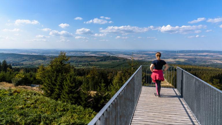 Pauline auf der Skulptur Windklang beim Genießen der Aussicht vom Erbeskopf, dem höchsten Berg in Rheinland-Pfalz