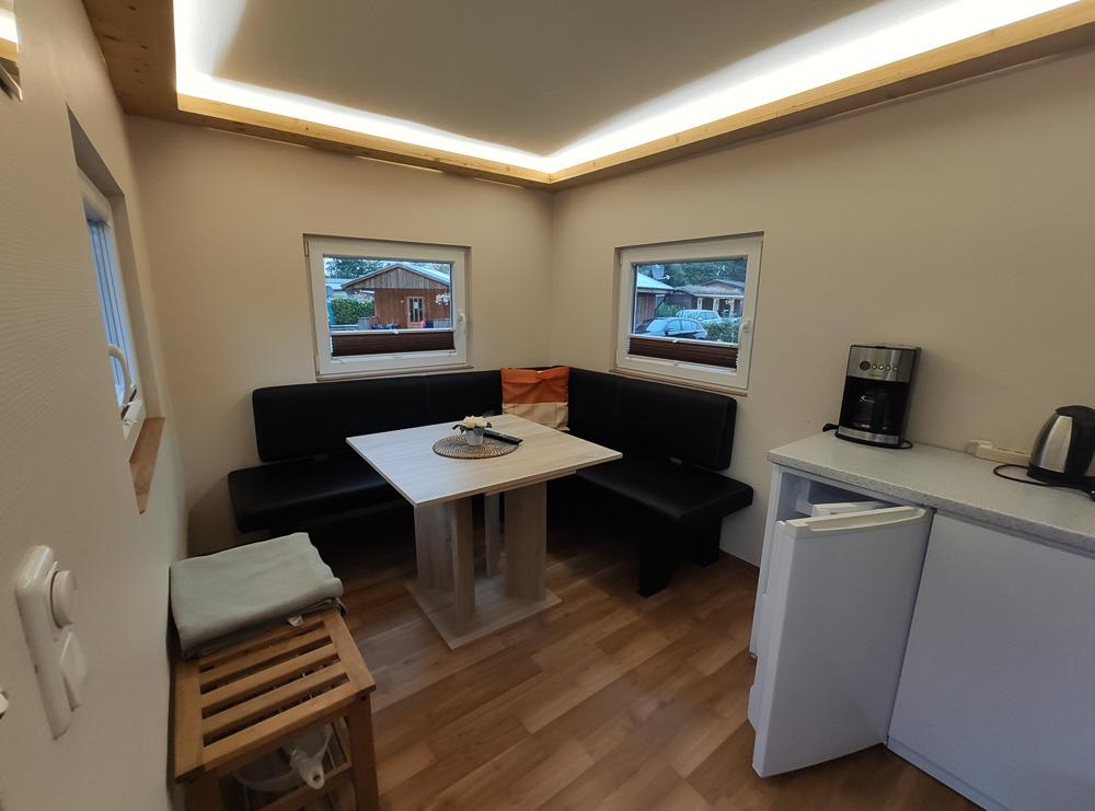 Gemütliche Sitzecke mit Tisch und kleiner Küchenzeile im Nordischen Holzhaus. Sogar einen eigenen Kühlschrank hat man praktischerweise dort.