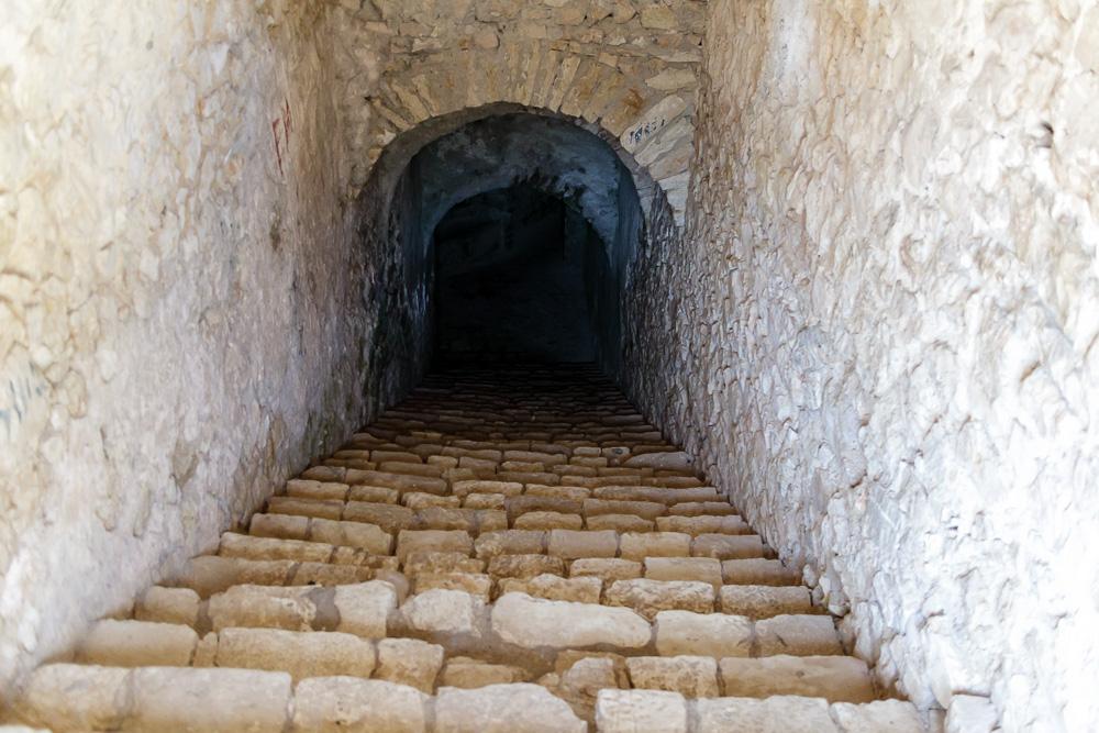 Die steinerne Treppe, welche vom Dach der Festung Porto Palermo hinunter ins Dunkle führt