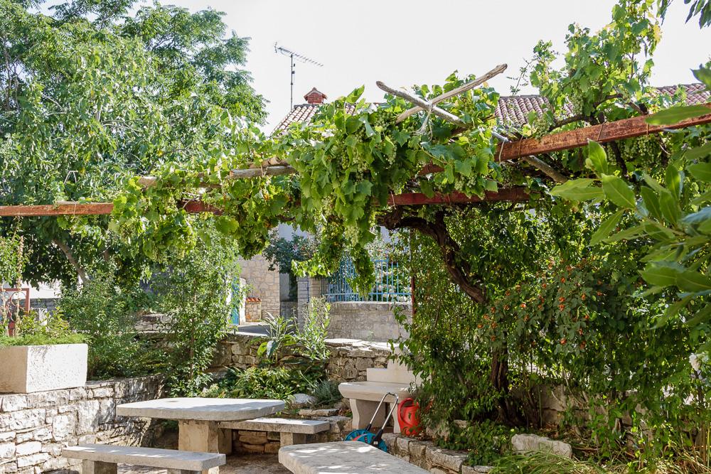 Der gemütliche Garten unseres Ferienhauses in Kroatien mit dem tollen Steintisch