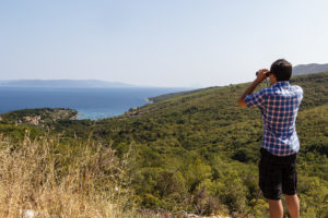Christian mit Fernglas auf der Halbinsel südlich von Labin während dem Ferienhausurlaub in Kroatien.