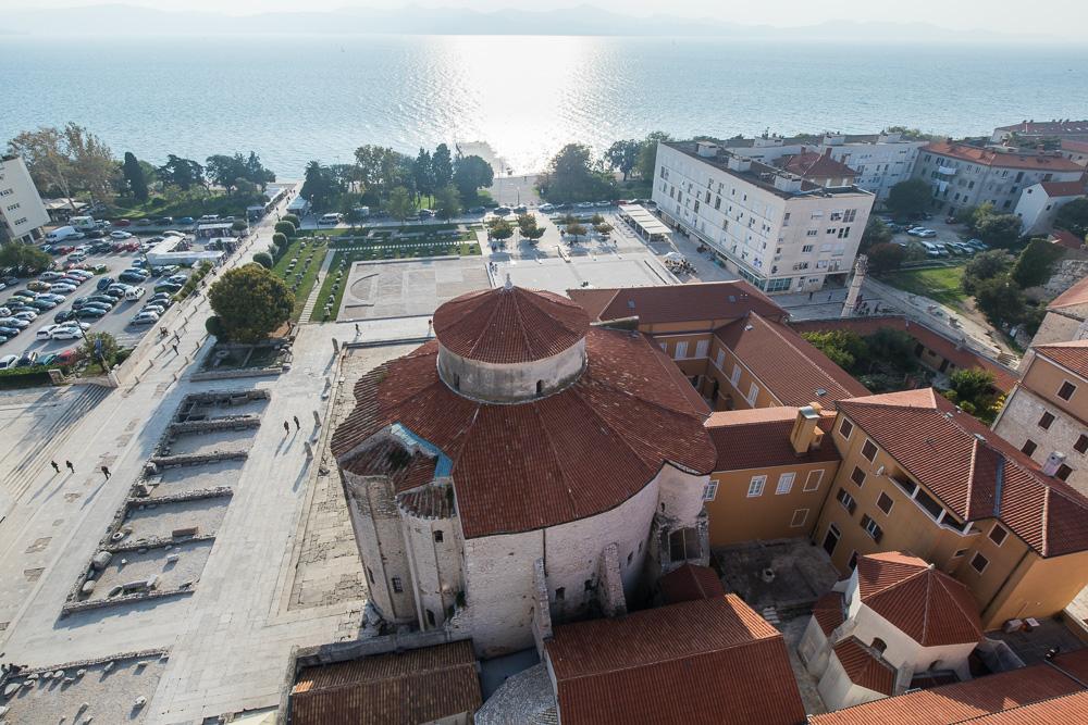 Die Donatus Kirche vom Turm der Kathedrale aus gesehen. Links im Bild die Überreste des Forums und im Hintergrund die Uferpromenade der Altstadt Zadars.