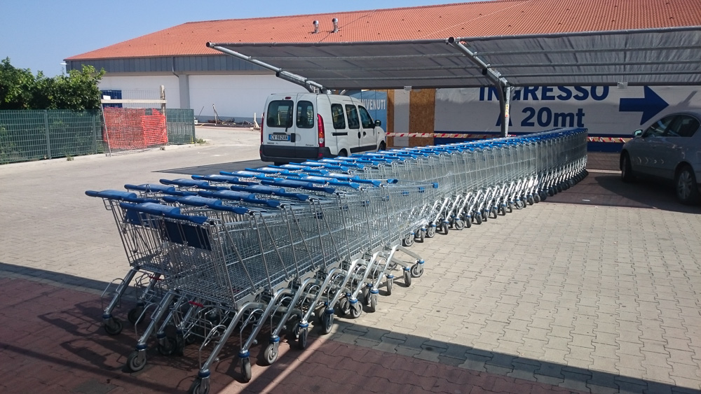 Lange Schlange an Einkaufswägen auf dem Parkplatz von Lidl in Rossano, Kalabrien